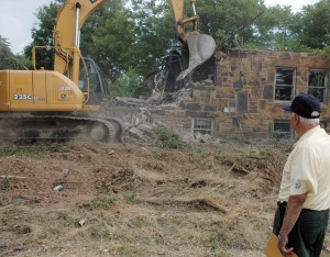 Workers demolish derelict house